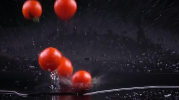 Zpomalený pohyb rajčat s vodou kapky na černém povrchu