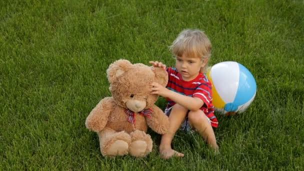 malý chlapec objímání medvídek na zelené trávě