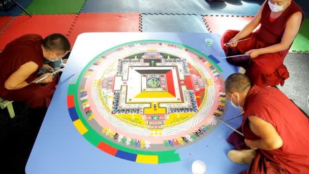 tři tibetskými mnichy usilovně pracuje na pískové mandaly