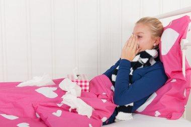 Sick teenager girl blowing nose