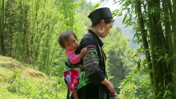 Akha woman carry baby