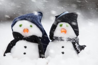 Two cute snowmen dressed for winter
