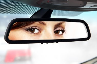 driver looks to rear-view mirror