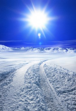 Snow covered road and sun