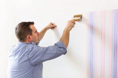 Handyman putting glue for a wallpaper