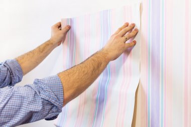 Handyman putting up wallpaper