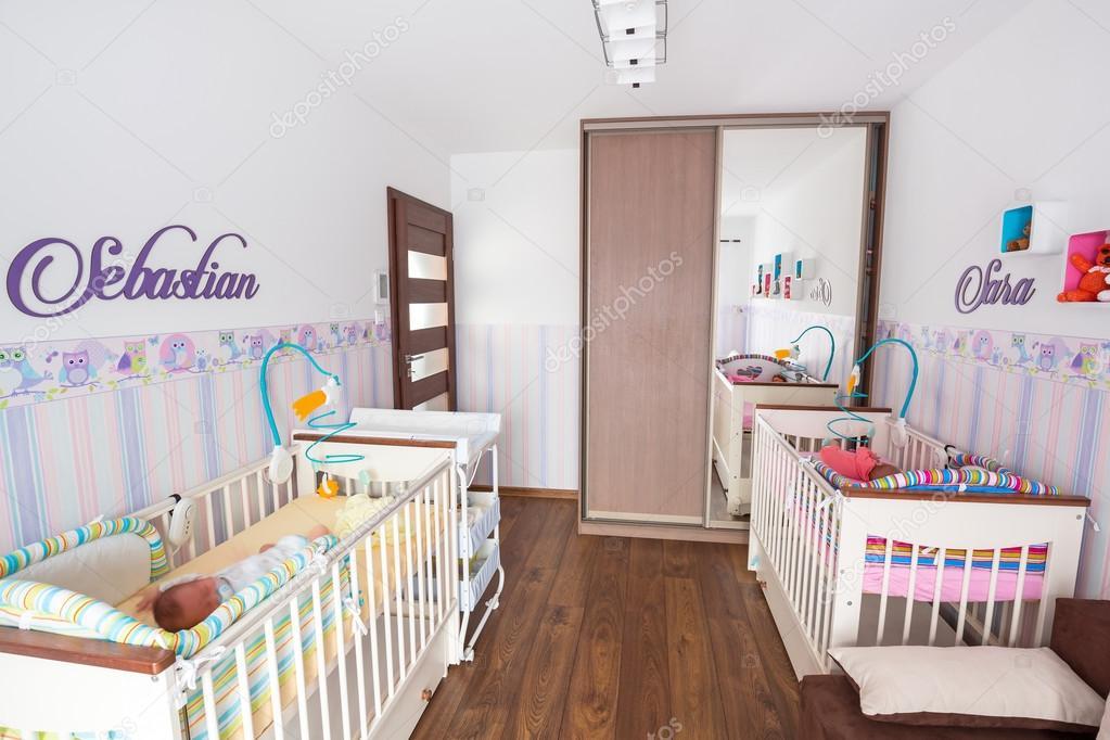 Baby tweeling kamer met pastel wallpapers u stockfoto