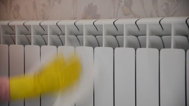 Weibliche Hand in Gummihandschuh reinigt Heizkörper