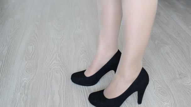 Woman takes off down a black high-heeled shoes