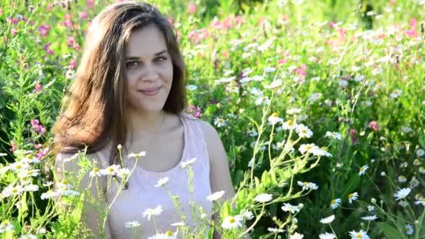 Vizsgálja a kamera ül a virág meadow hosszú hajú lány