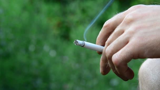 Mann mit Zigarette vor dem Hintergrund der Natur