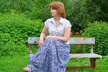 adult woman sitting on a bench in the garden