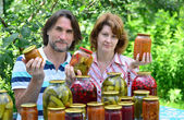 Photo  couple of middle age with homemade preserves and jams