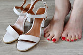 Womens legs and white sandals