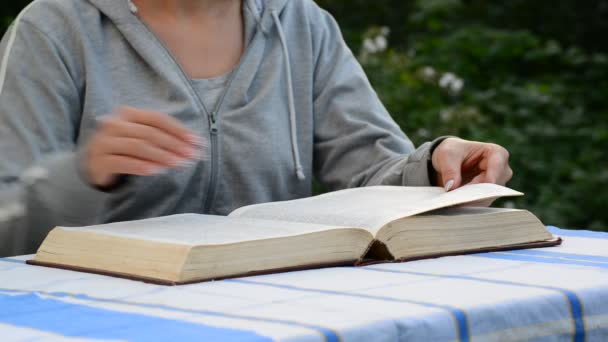 Frau liest ein Buch im Garten