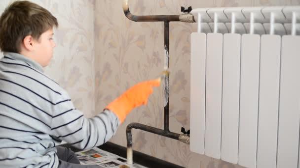 Kluk maluje topení v bytě