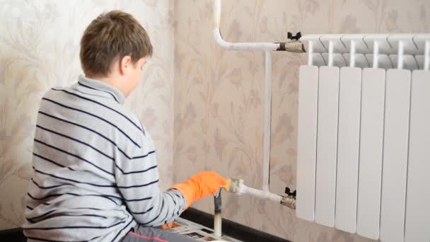 Junge streicht Heizkörper in Wohnung