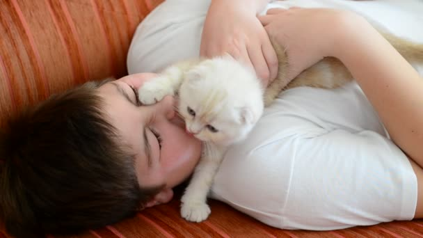 Teenage boy playing with a kitten on  couch