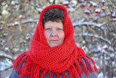 Starší žena v červené pletený šátek na hlavu venku