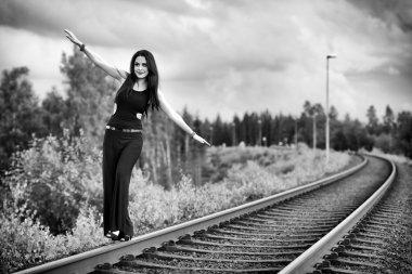 Brunette woman walking on the railroad