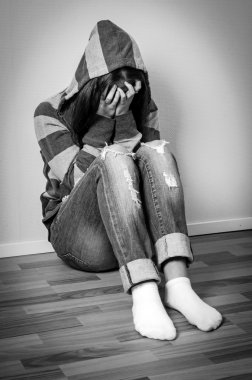 Depressed girl in hooded sweatshirt