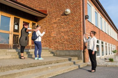 Waving goodbye in first school day