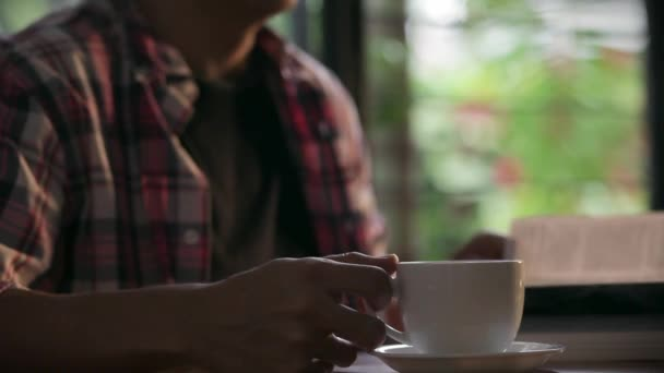 Egy könyvet olvas, és kávét iszik az ember