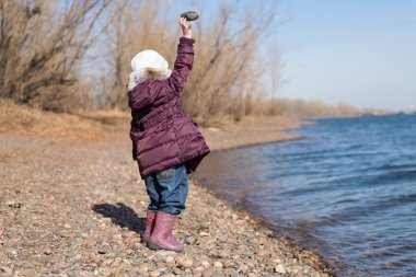 Little girl throwing stones into river