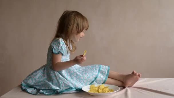 Dívka se pohybuje nohama a jedl brambůrky