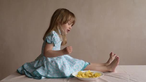 Dívka s brambůrky, za stálého míchání ji prsty