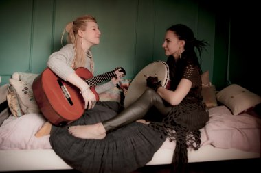 two beautiful woman with  tambourine and guitar