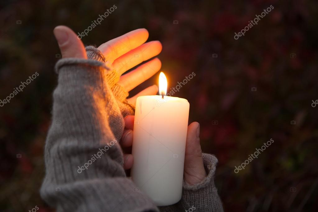 Young woman looking to a candle Praying Hands with candle in dark background
