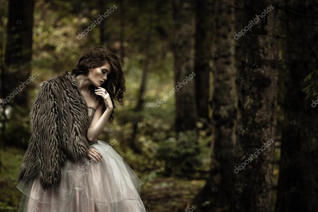 Portrait of romantic woman in beautiful dress in forest