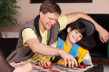 Disabled boy in wheelchair playing checkers with father at home