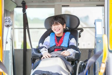 Smiling disabled boy in wheelchair on yellow school bus lift