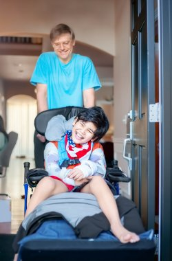 Father pushing disabled son in wheelchair out the front door