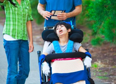 Disabled child in wheelchair outdoors with caregivers or family
