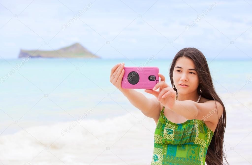 Beautiful biracial Thai Caucasian teen girl standing on tropical Hawaiian  beachi holding camera taking pictures or videos — Photo by jarenwicklund