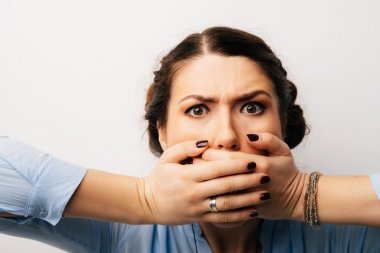 girl covers mouth with hands