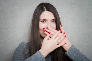 girl covering mouth with hands
