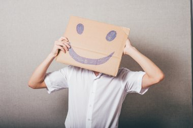 man holding a cardboard with a smiley