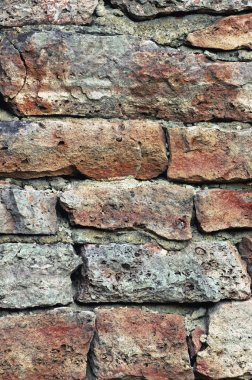 Stone wall macro closeup, stonewall pattern background, vertical, old aged weathered red and grey grunge limestone dolomite calcium carbonate hard sedimentary slate slab rock texture, natural grungy textured bricks, beige, yellow, reddish, gray brick