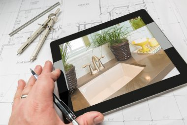 Hand of Architect on Computer Tablet Showing Home Illustration Over Plans
