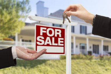 Agent Handing Over House Keys in Front of New Home