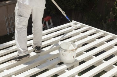 Painter Rolling White Paint Onto Top of Patio Cover