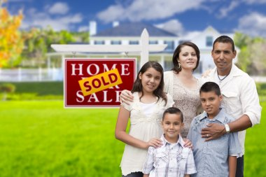 Hispanic Family in Front of Sold Real Estate Sign, House