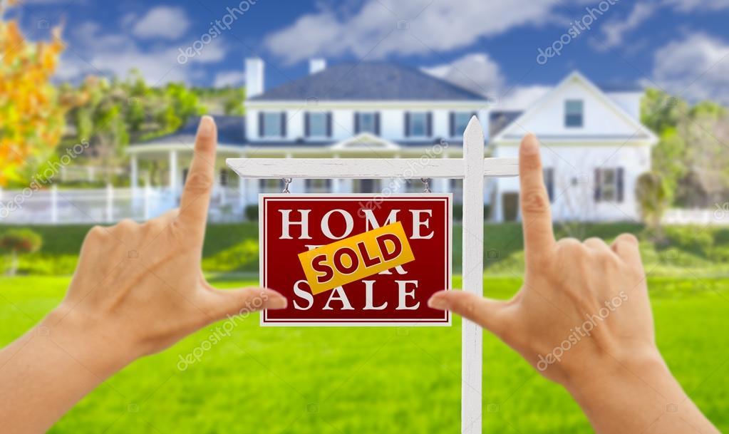 Manos enmarcando vendieron por casa y signo de venta inmobiliaria ...