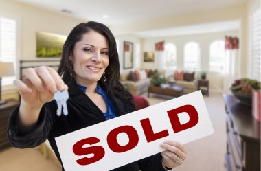 Hispanic Woman with Keys and Sold Sign in Living Room