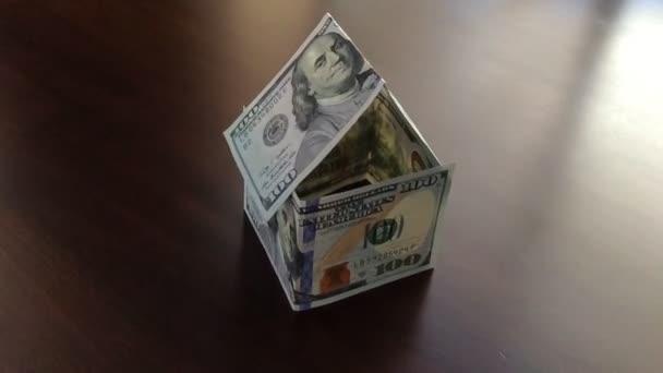 Zeitlupe schwenkt Papiergeldhaus auf dunklem Holztisch weg