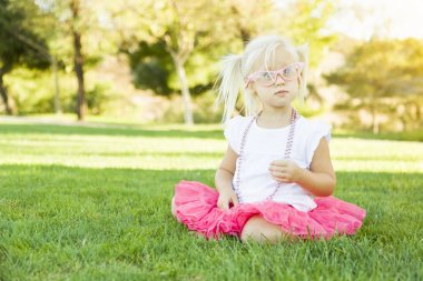 Little Girl Playing Dress Up With Pink Glasses and Necklace
